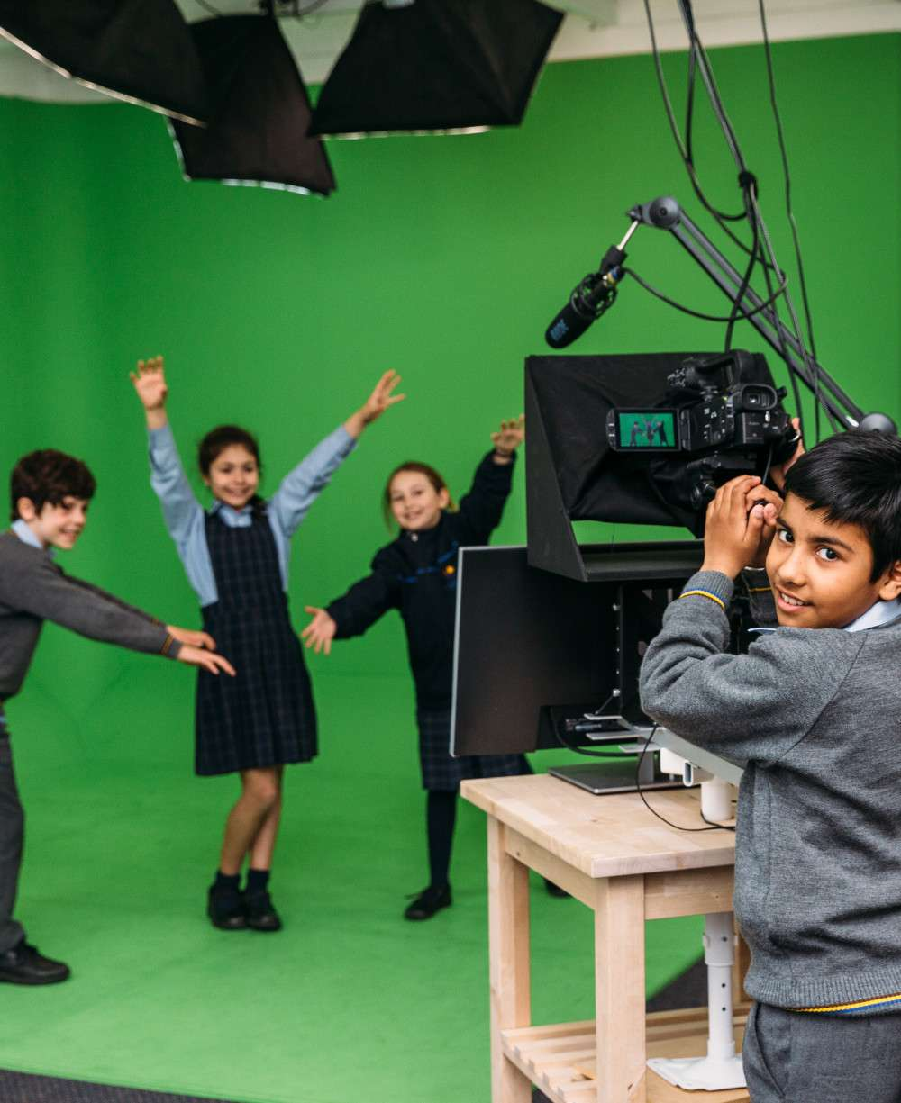 Students filming on a green screen